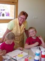 Les joies de la peinture avec la peintre et deux enfants du groupe.