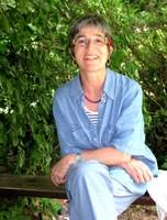 L'artiste assise sur un banc dans la nature qu'elle affectionne