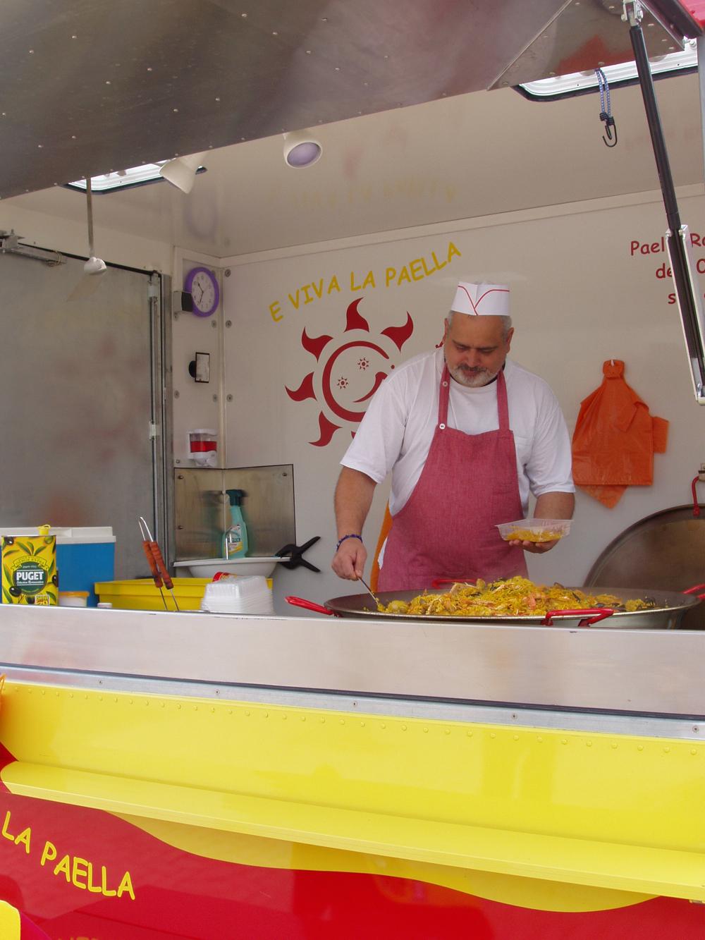 M. Girard remplissant une barquette dans son camion E Viva La Paella