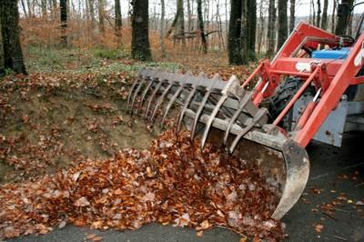 la grosse m choire du tracteur qui ramasse les nombreuses feuilles mortes sur un sentier. Black Bedroom Furniture Sets. Home Design Ideas